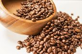 Closeup Of Woodden Bowl With Heap Of Arabica Coffee Beans On White Surface. Light Effect Used