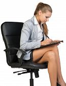 Businesswoman sitting on office chair with clipboard and writing