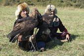 Men hold golden eagles (Aquila chrysaetos) in Almaty, Kazakhstan.