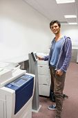 Smiling student standing next to the photocopier at the university