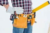 Cropped image of repairman wearing tool belt while standing with hands on hips over white background