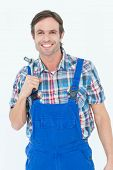 Portraiot of confident plumber holding tool over white background