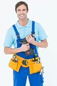 Portrait of confident carpenter holding drill machine over white background