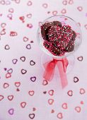 picture of glass heart  - Glass full of chocolate heart cookies sits on a soft pink background with glitter hearts - JPG