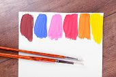 Colorful paint strokes with brush on white sheet of paper on wooden table background