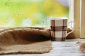 Cup of hot drink with sackcloth on windowsill on rain background