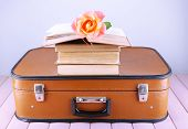 Vintage suitcase with pile on books on patterned surface and light background