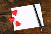 Blank sheet of paper with hearts and pen on rustic wooden table background