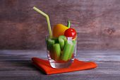 Sticks of celery with sweet pepper and cherry tomato in glass with tube and napkin on rustic wooden background