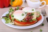 Sandwich with poached eggs, bacon and vegetables on plate on wooden background