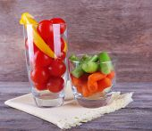 Two glasses with vegetables on rustic wooden background