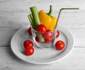 Vegetables in glass with tube on plate and on color wooden planks background