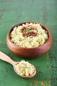 Rice with walnuts and rosemary in plate on color wooden table background