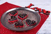 Romantic still life with cookies in form of heart on metal tray and color wooden planks background