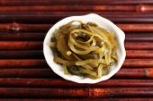 Seaweed in white bowl on bamboo mat background