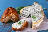 Blue cheese with sprigs of rosemary and bread on sheet of paper and color wooden table background