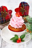 Cup-cake on saucer with Christmas decoration on color wooden table background