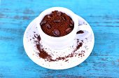 Coffee beans in white ceramic cup with saucer on blue wooden background