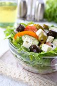 Greek salad in glass dish on napkin and wooden table background