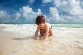 Little boy enjoys summer day at the tropical beach.