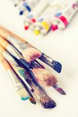 Paintbrushes Closeup And Oil Multicolor Paint Tubes On White Artist Canvas