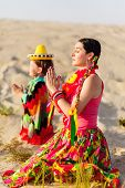 son and mother dressed in Mexican clothes praying together