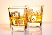 image of whiskey  - a pair of glasses of whiskey with ice on white bar table - JPG