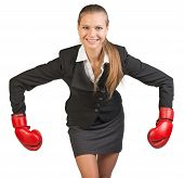 Businesswoman wearing boxing gloves bending forward with her arms bent and outstretched