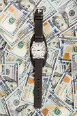 Wrist watch on money background