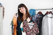picture of dress-making  - Beautiful young woman near rack with clothes making chioce with several dresses in her hands - JPG