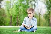 picture of sad boy  - portrait of a young sad boy with book on green grass - JPG