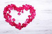 foto of hydrangea  - Petals of pink hydrangea in shape of heart on wooden background - JPG