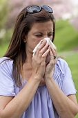 stock photo of hay fever  - Woman outside blowing nose with a tissue - JPG