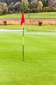 pic of flag pole  - a golf hole with a flag pole in a beautiful golf course - JPG