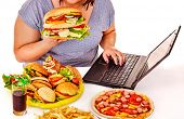 foto of high calorie foods  - Body part of woman eating fast food at work - JPG