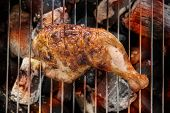 pic of flame-grilled  - Grilled chicken thigh over flames on a barbecue - JPG
