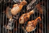 picture of flame-grilled  - Chicken legs grilling over flames on a barbecue - JPG