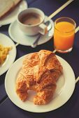 image of breakfast  - Croissant Breakfast served with black coffee and a breakfast menu such as orange juice jam eggs filling it - JPG