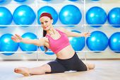 picture of do splits  - fitness woman instructor doing stretching pilates exercises split in sport club - JPG