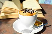 foto of treble clef  - Cups of cappuccino with treble clef on foam  and book on table in cafe - JPG
