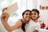 foto of bonding  - Smiling mother and daughter bonding together to take a selfie - JPG