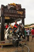 stock photo of carnival ride  - RUSTENBURG SOUTH AFRICA - MAY 25: Black African Boy riding on electronic horse ride at Rustenburg Fair on May 25 2014 in Rustenburg South Africa.
