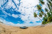 stock photo of tropical island  - Boat At The Seashore on a tropical island on a tropical island photographed with fisheye lens  - JPG