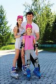image of roller-skating  - Daddy and two daughters skate on roller skates on a warm summer day - JPG