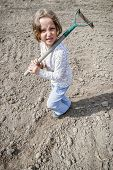 stock photo of hoe  - Girl standing with hoe during preparation to plant - JPG