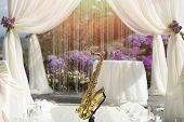 stock photo of saxophones  - Gold saxophone in festive wedding ceremony decoration of lightweight white fabric on purple and violet natural background horrizontal picture - JPG