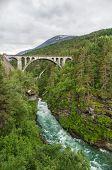image of cross hill  - Railway arch bridge Kylling crosses rapid river Rauma Norway - JPG