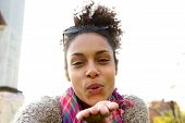 picture of blowing  - Selfie portrait of an attractive young woman blowing a kiss - JPG