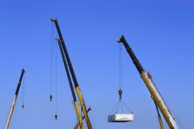 stock photo of boom-truck  - Building site with the crane trucks that unloads trucks and works on construction - JPG