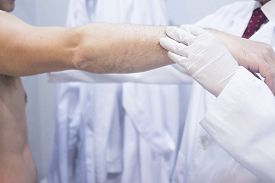 pic of elbow  - Male Traumatologist orthopedics surgeon doctor examining middle aged man patient to determine injury pain mobility and to diagnose medical treatment in shoulder arm elbow and wrist - JPG